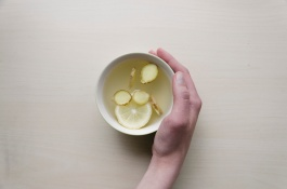 Public domain image of a hand holding a bowl of lemon water.